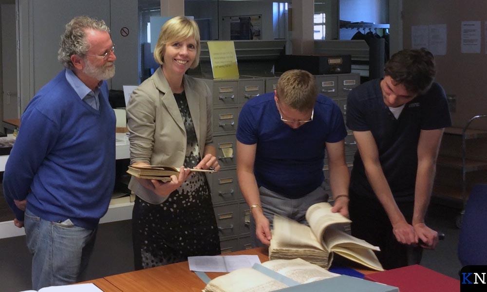 Fred van de Kraaij komt met een vraag naar het Stadsarchief die gemeentearchivaris Margreet Vink-Bos, Otto Ottens en Michiel van Wijngaarden opzoeken.